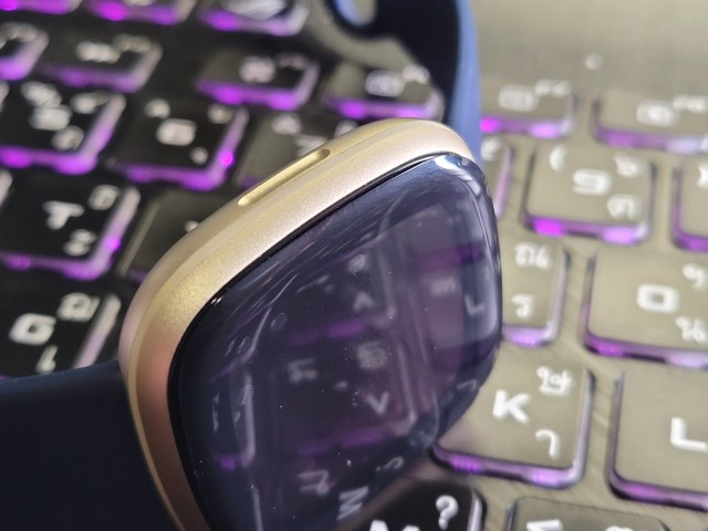 ภาพระยะใกล้ของหน้าจอ Fitbit Versa 3 หลังจากติดฟิล์มกันรอยไม่สำเร็จ เห็นฟองอากาศที่ยังค้างอยู่ เพราะมีฝุ่นเกาะหน้าจอ