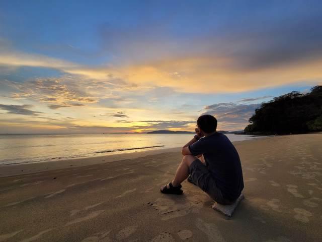 ด้านหลังของผู้ชายที่กำลังนั่งอยู่บนหาดทราย มองไปที่ทะเล ยามพระอาทิตย์ตกดิน