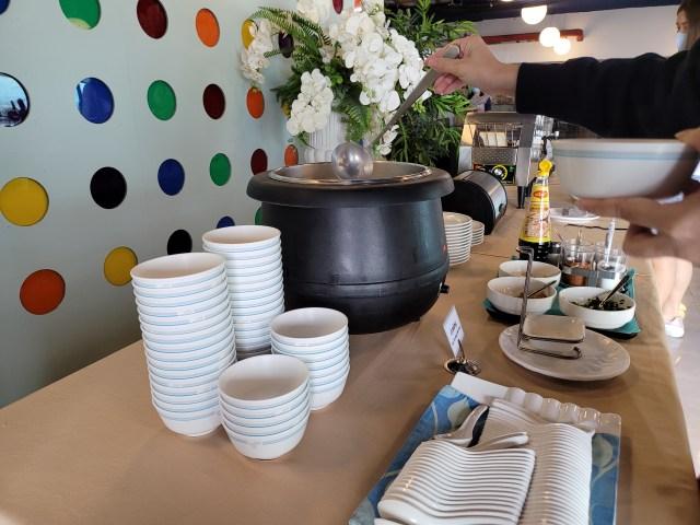 ไลน์อาหารเช้าของโรงแรม Friday มีถ้วยและช้อนเรียงซ้อนกันอยู่ มีหม้อข้าวต้ม และเครื่องปิ้งขนมปัง