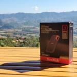 กล่องใส่ SanDisk Extreme Portable SSD V2 1TB วางอยู่บนโต๊ะไม้ไผ่ มีวิวด้านหลังเป็นภูเขาและท้องฟ้า