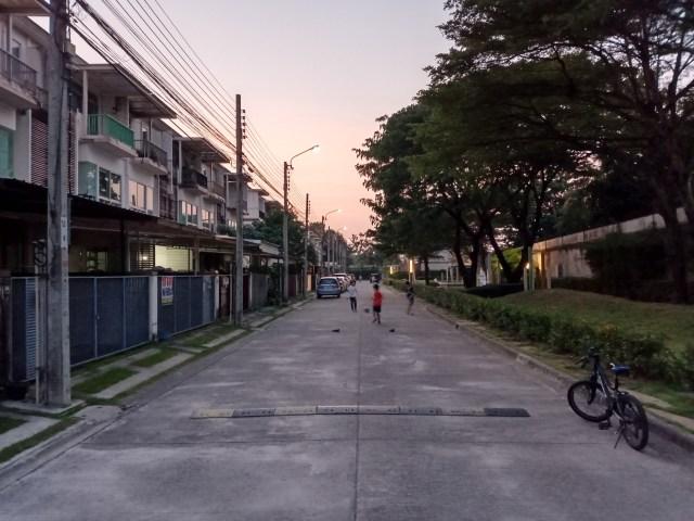 ภาพของถนนภายในหมู่บ้านจัดสรรแห่งหนึ่งในยามเย็น มีเด็กๆ กำลังออกมาเล่นฟุตบอล มีจักรยานจอดที่ริมฟุตบาธ