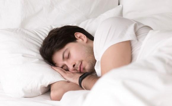 ชายหนุ่มกำลังหลับอยู่บนเตียง โดยสวมสมาร์ทวอทช์เอาไว้ด้วย