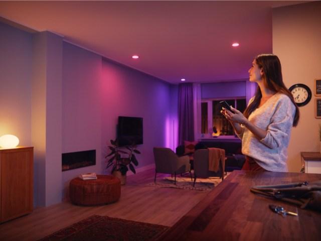 ภาพแสดงตัวอย่างการใช้งานหลอดไฟอัจฉริยะ Philips Hue เป็นห้องนั่งเล่นที่มีชุดเก้าอี้ และโทรทัศน์ติดผนัง ไฟในห้องมีโทนสีม่วง มีผู้หญิงชาวต่างชาติกำลังใช้สมาร์ทโฟนในการสั่งงานอยู่