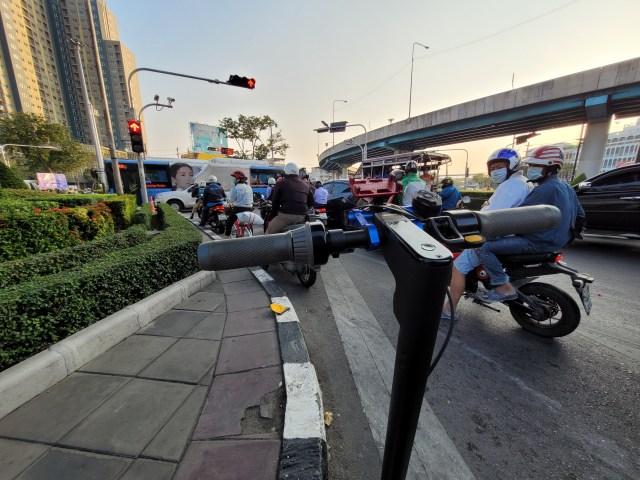 ภาพมุมกว้าง แสดงให้เห็นส่วนคอและแฮนด์ของสกู๊ตเตอร์ไฟฟ้า Ninebot Kickscooter MAX ที่กำลังจอดติดไฟแดงอยู่ มีรถ