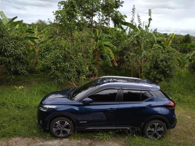 รถยนต์ Nissan Kicks จอดอยู่โดยมีแบ็กกราวด์เป็นต้นไม้ต่างๆ และต้นกล้วย
