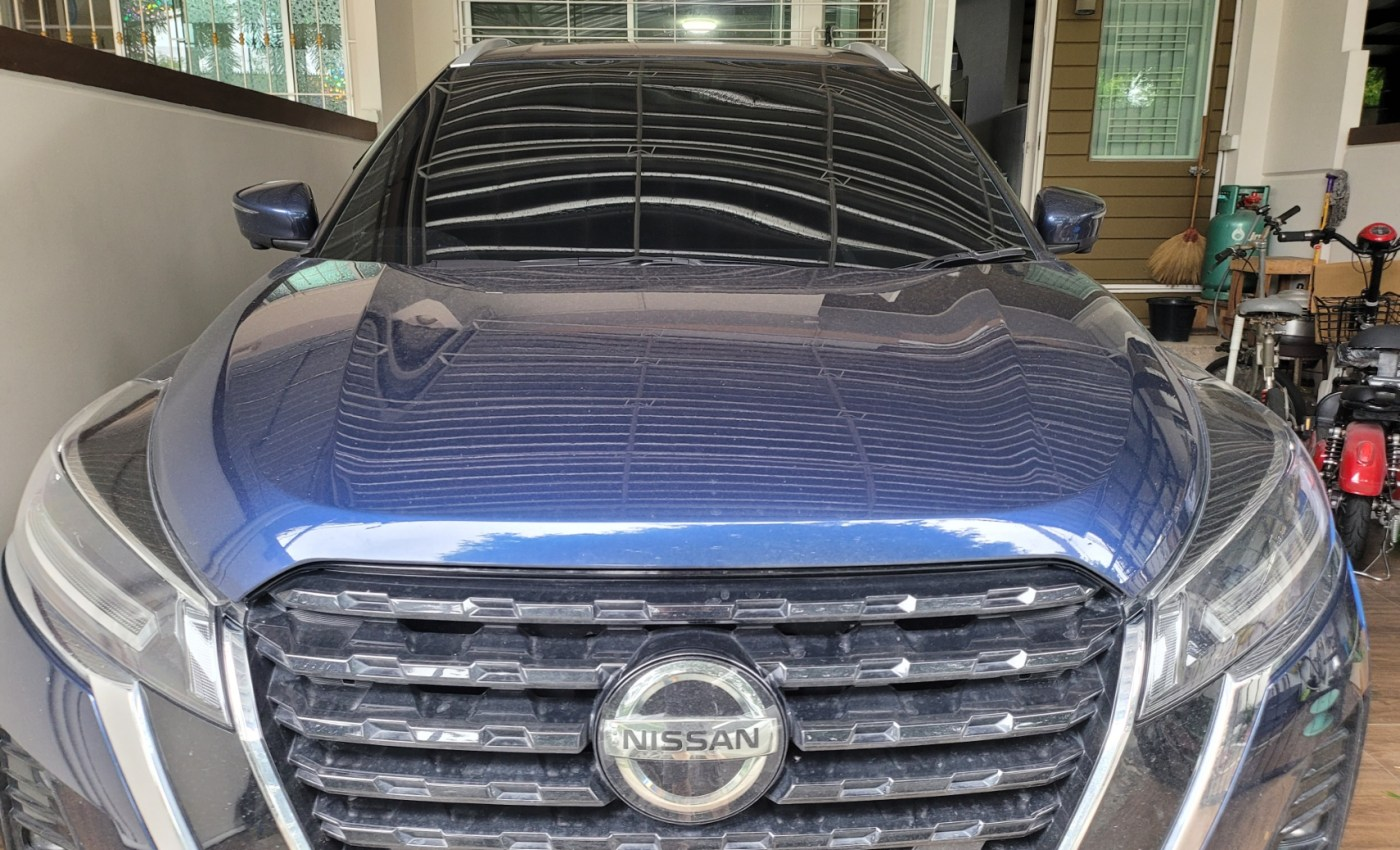 ด้านหน้าของรถยนต์ Nissan Kicks ที่จอดอยู่ในที่จอดรถที่บ้าน