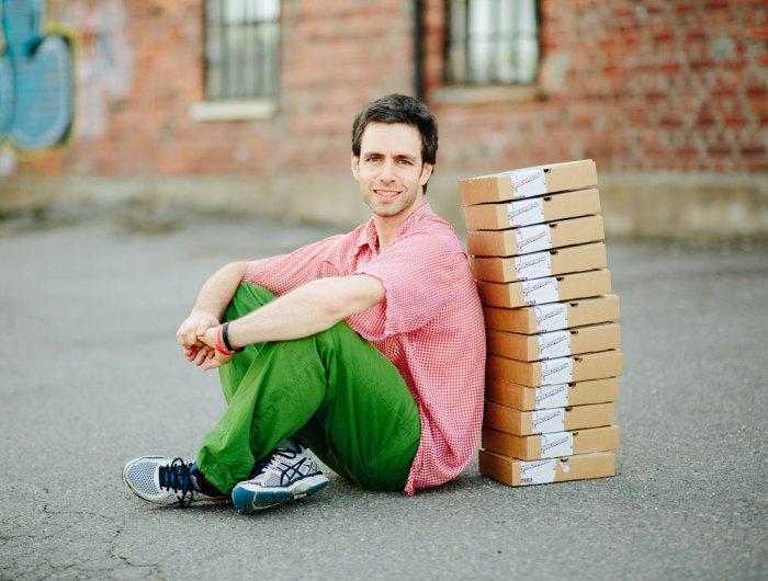 Bilde av mann som sitter på bakken med kaffebokser