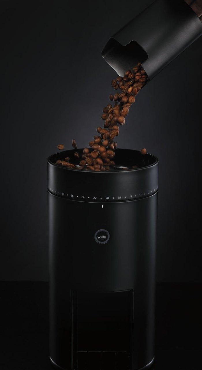 Bilde av kaffebønner som helles i en kvern fra Wilfa