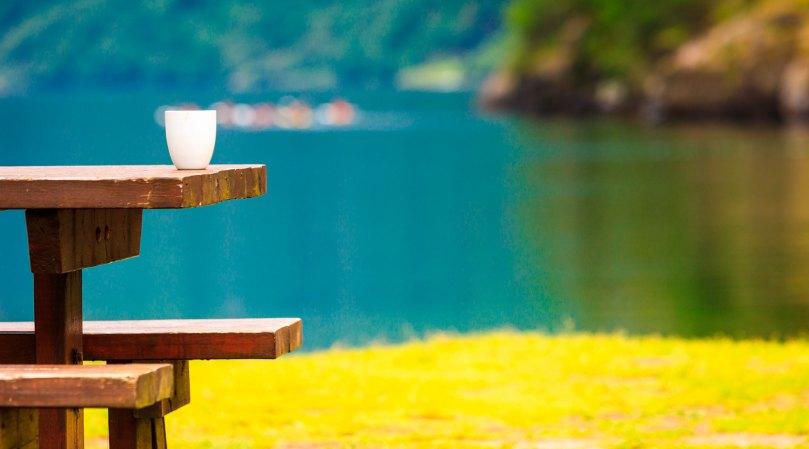 benk med kaffekopp ved fjorden