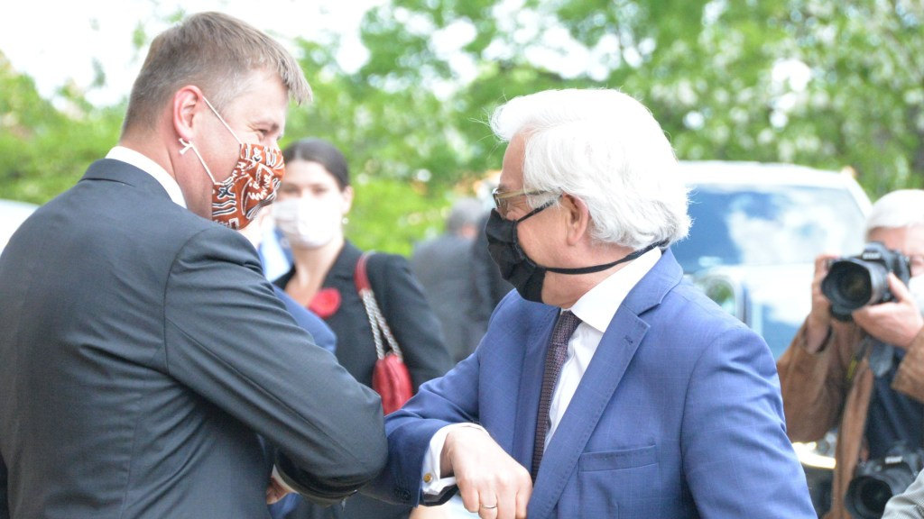 "Czech Foreign Minister Tomas Petricek greets his Polish counterpart with an ""elbow-bump"" in Prague"