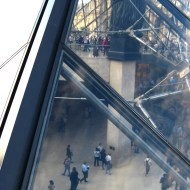Looking down inside the main Louvre pyramid at the people below.