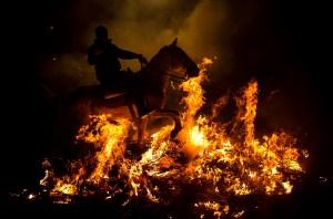 Riding through bonfire smoke in celebration of Saint Anthony in San Bartolomo de Pinares, Spain. Source: clikhear.palmbeachpost.com
