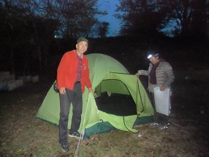 朝、まだ暗い中でテントをたたむ