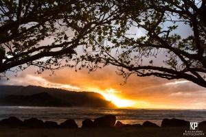 As the sun sets behind Mt. Makana, the sky lights a fire