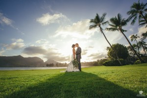 Kauai wedding photographer, Kahahawai Photography captures a stunning photo of the sun setting behind a local couple just moments after the I do's!