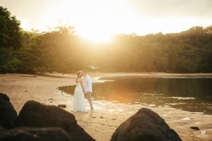 Kauai Photographer captures newlyweds kissing on the beach in front of a gorgeous sunset