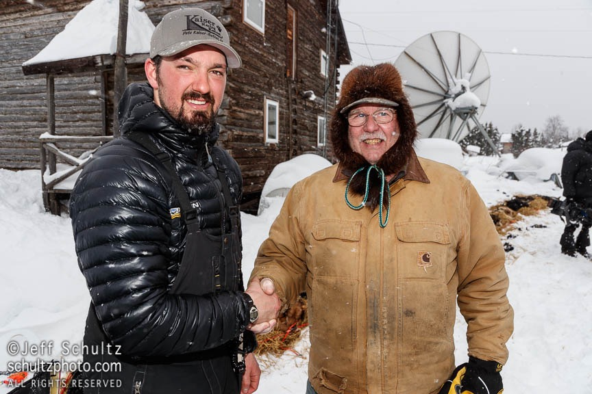 Kaltag checker Richard Burnham congratulates Pete Kaiser as the winner of the Bristol Bay Native Corporation's FISH FIRST award for being the first musher to reach the Kaltag checkpoint on Saturday March 9th during the 2019 Iditarod Trail Sled Dog Race. Photo by Jeff Schultz/ (C) 2019 ALL RIGHTS RESERVED
