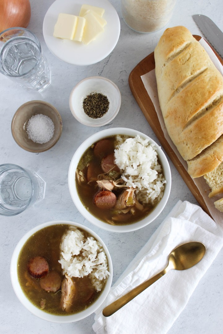 Dry Roux Gumbo in a bowl with rice and French bread in the background.