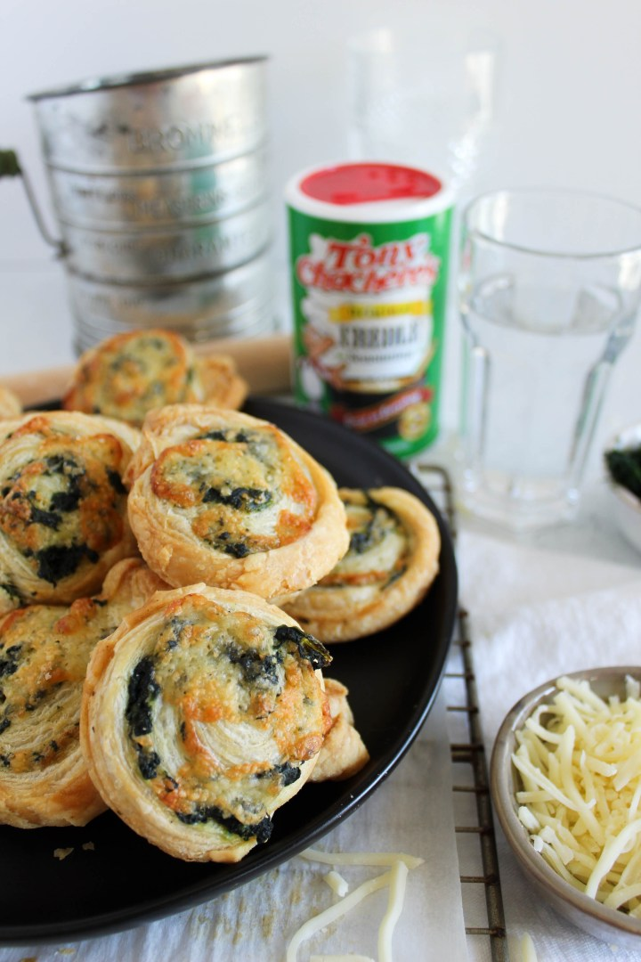 spinach pinwheels on a plate with Tony's Chachere's seasoning in the background.