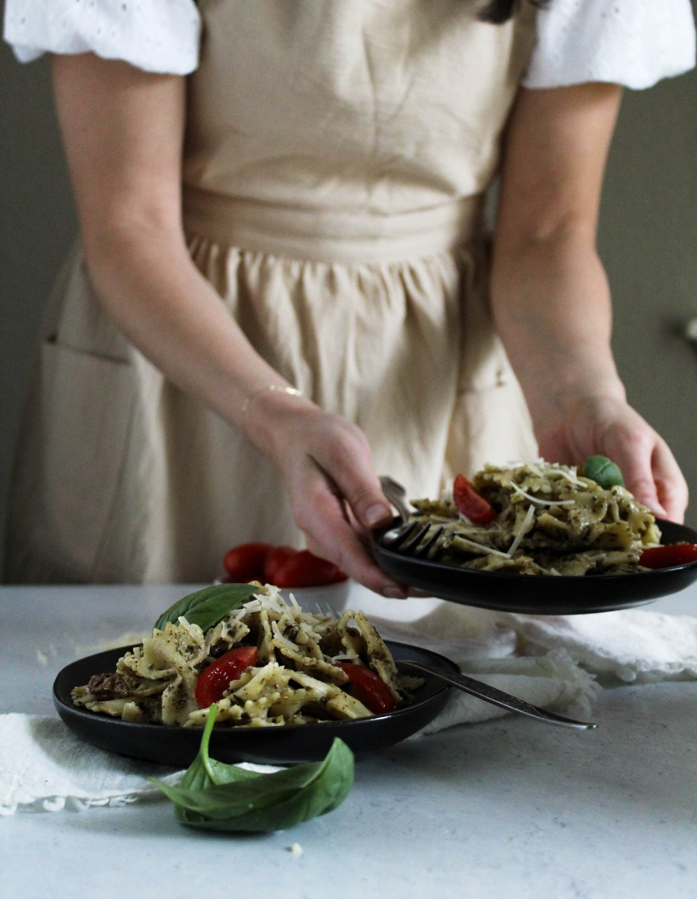 Kait serving a plate of pesto pasta.