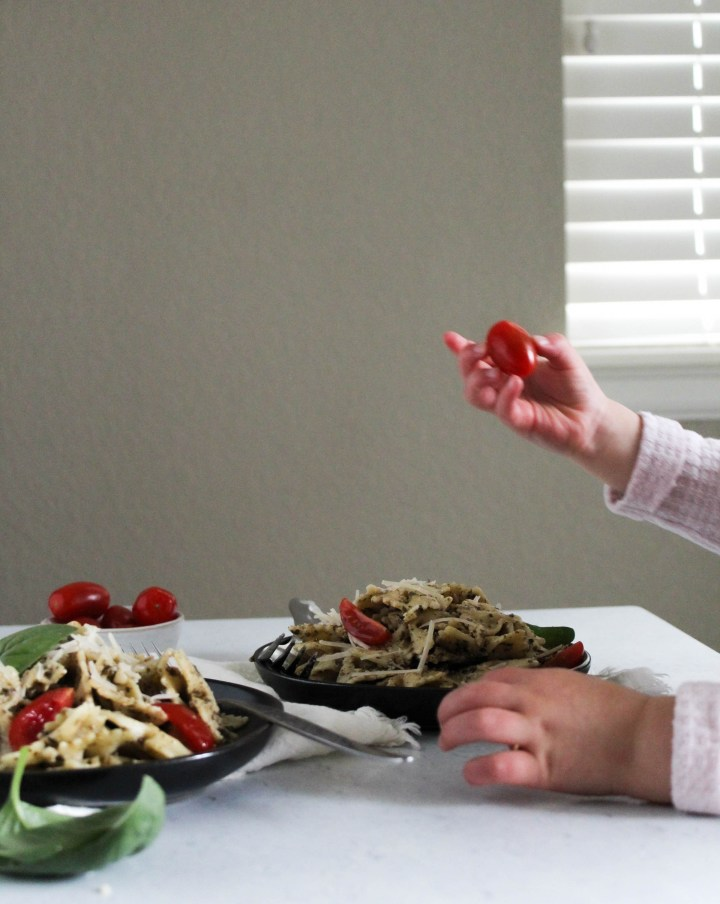 View of a toddler grabbing a cherry tomato from the pesto pasta plate.