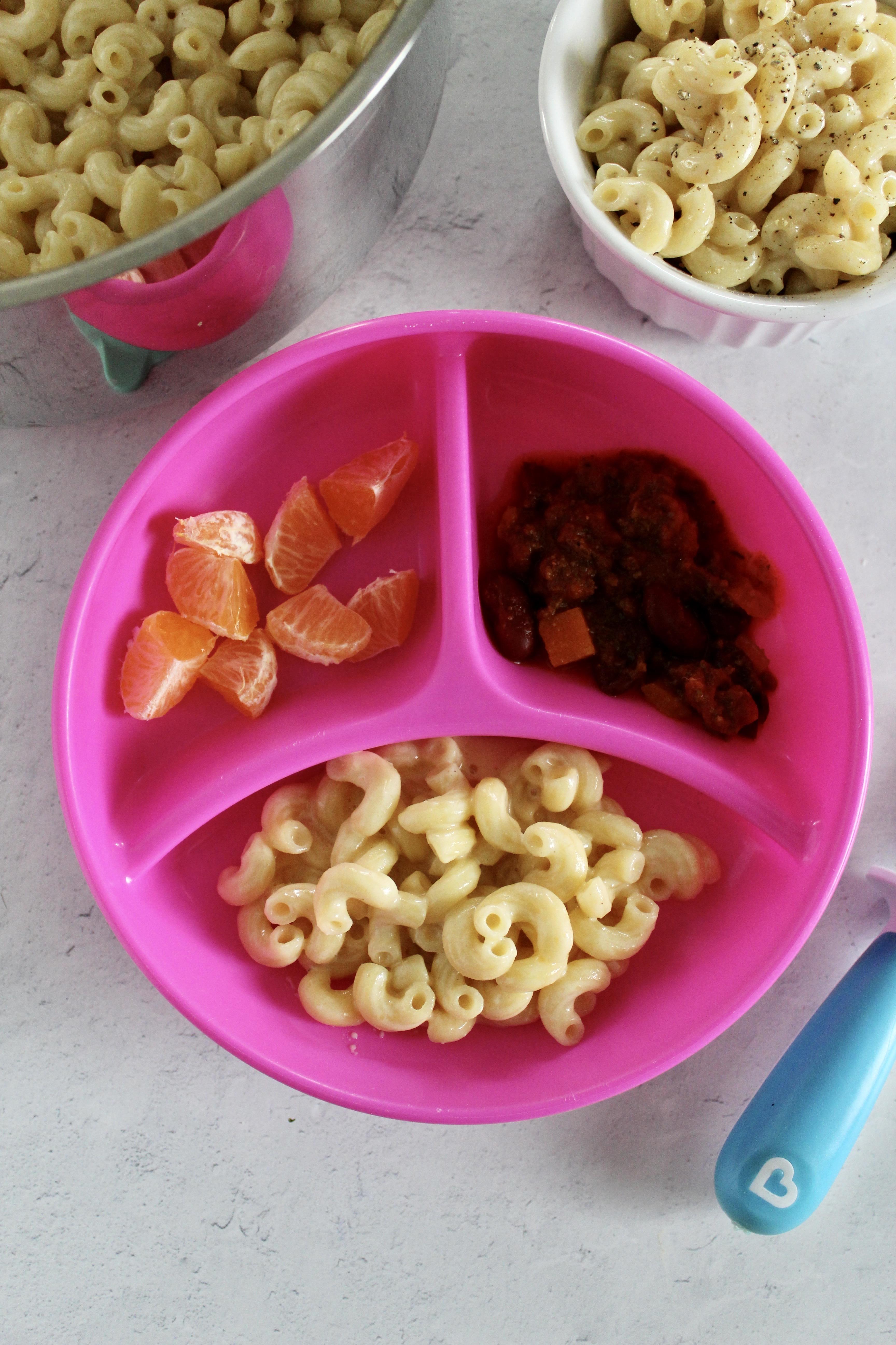 child's plate of Mac and cheese, orange, and chili