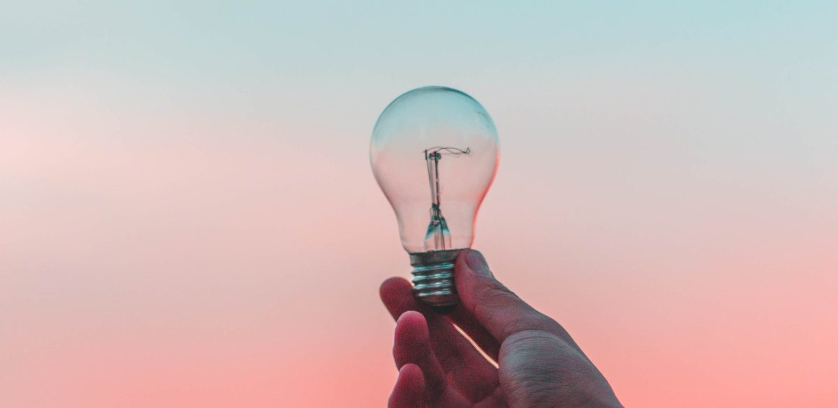hand holding a lightbulb on a pink blue wash background, ideas, inspirational