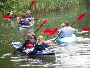 Większa rodzina na kajakach w rzece Piaśnica