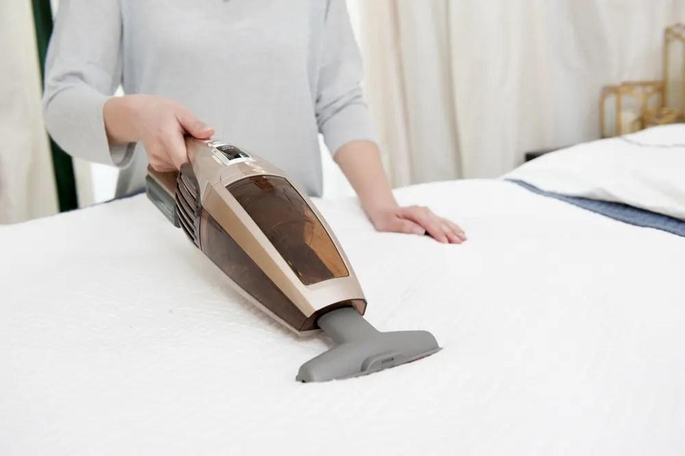 マットレスのダニ掃除をする女性
