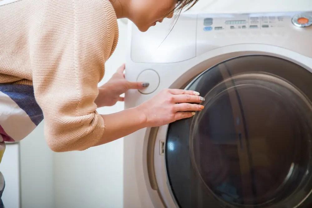 洗濯機掃除でカビアレルギー対策をする女性