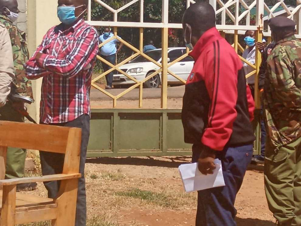 Oloosirkon-Sholinke MCA in red jersey is guarded by police at Kajiado open air law court before taking a plea on Monday.