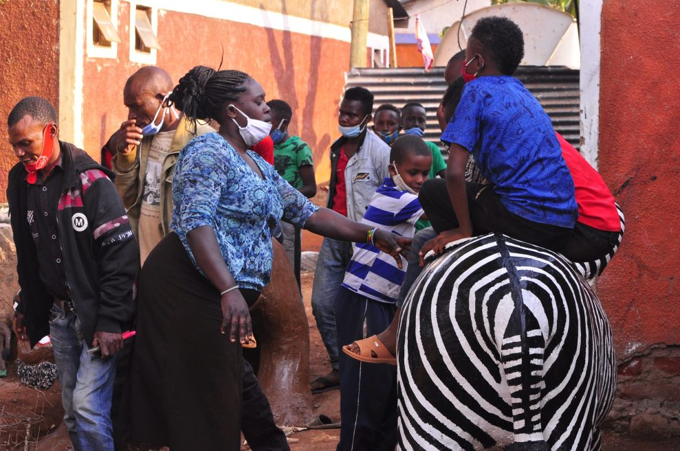 Art teacher Michael Kimanzi and parent Catherine Mbula pose with the children sitting on a sculture of a zebra on August 10.