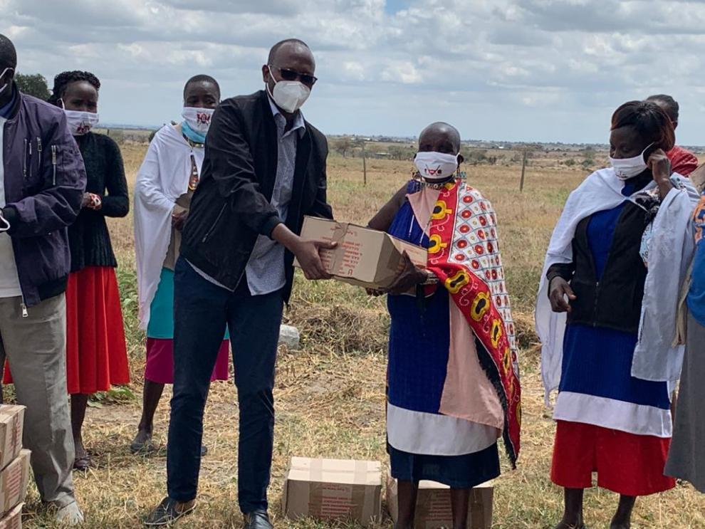 Kajiado COVID-19 Partners' Coordination Committee chairman Daniel Kanchori hands over food donation to residents of Lenjani today .