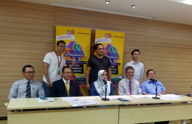 The artistes who are expected to DJ at the carnival and entertain visitors pose with Rosnani Mahamad Zain, Head of Bank Negara Malaysia Office Kuching (seated, middle) and (from left, seated) Abdul Malek Abdullah, Regional Head of Bank Islam, Nasir Khan, Chairman Association of Bank Sarawak, Chua Ko Onn, Regional Secretary, Association of Bank Sarawak, Tommy Li Chiau Tong, President Pertubuhan Insuran Sarawak.