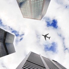 2015-11-Unsplash-PlaneFlyingOverSkyscrapersp-AirTransExec-Blue-Teaser-01