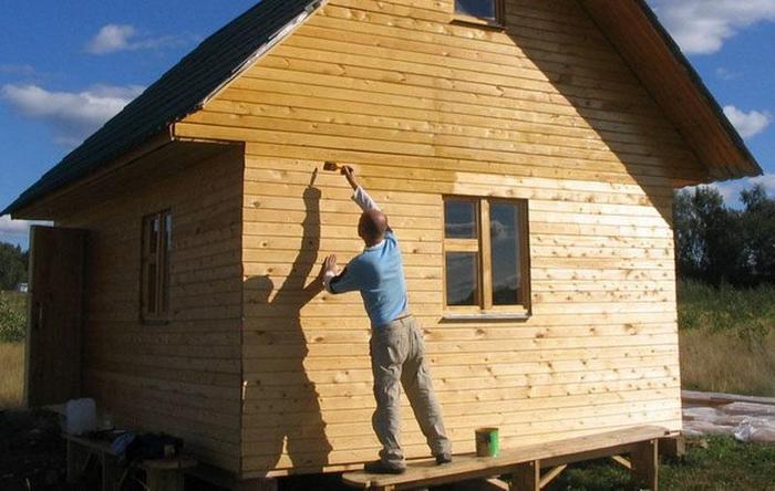 تنظیم سایدینگ با دستان خود را بر روی یک خانه چوبی