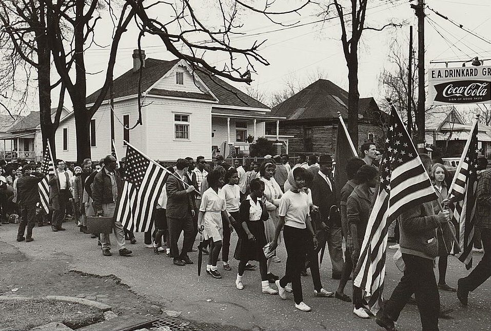 Participants, some carrying American flags, marching in the civil rights march from Selma to Montgomery, Alabama in 1965. Photo by Peter Pettus. Source: Library of Congress.
