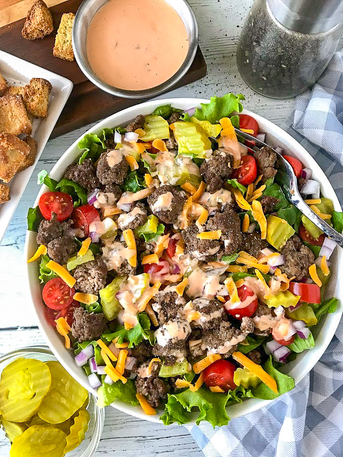 A further back picture of a cheeseburger bowl with croutons, dressing and pickles on the side