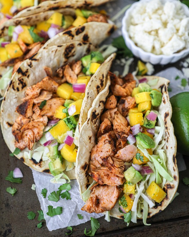 Spicy salmon tacos with cabbage and mango salsa sitting on a tray served with cilantro and extra lime wedges