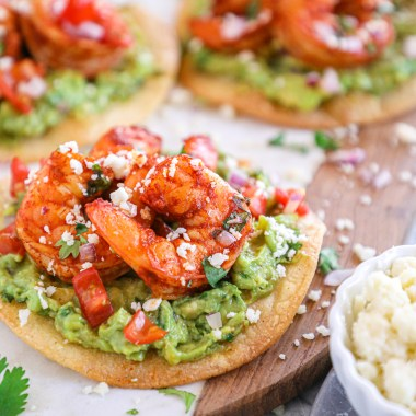 Chili lime shrimp tostadas with guacamole, chopped tomatoes and cotija cheese sitting on a marble plate served with extra cotija and lime wedges on the side