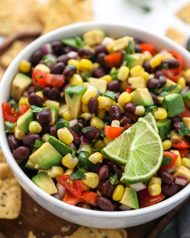 Black bean, corn and avocado salsa served in a white bowl with lime wedges and tortilla chips on the side