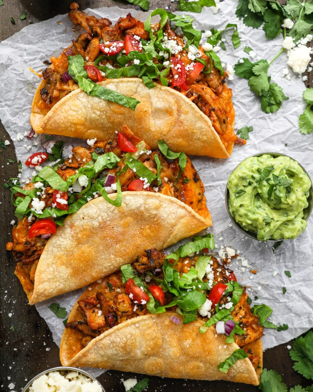 Chicken carnitas baked inside a crispy corn tortilla. They're served with tomatoes, lettuce and a creamy avocado sauce.