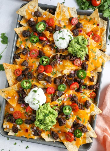 Carne asada nachos in a gray sheet pan topped with guacamole, sour cream, tomatoes and red onion