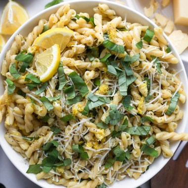 A large white bowl filled with lemon basil pasta salad with a lemon wedge and parmesan cheese and fresh basil sprinkled on top