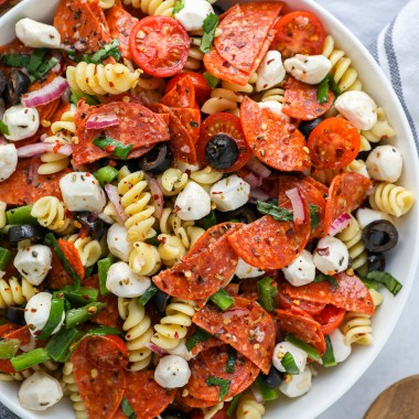 A white bowl filled with pizza pasta salad sitting on a marble countertop next to a wooden spoon