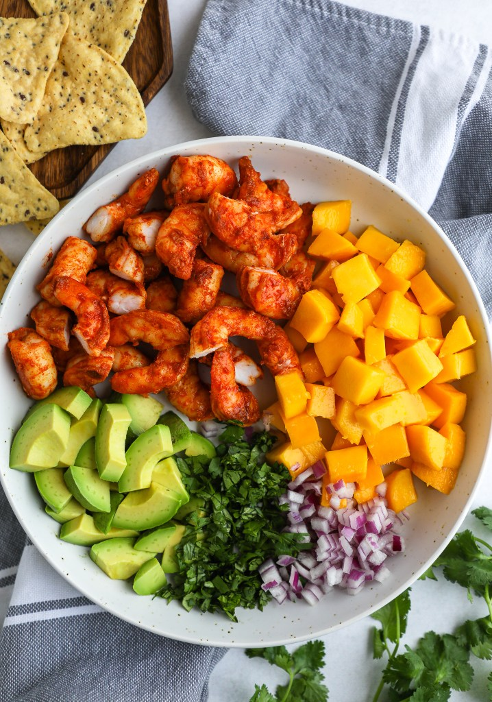 Ingredients to make a shrimp, mango and avocado salad in a white bowl with cilantro and onion