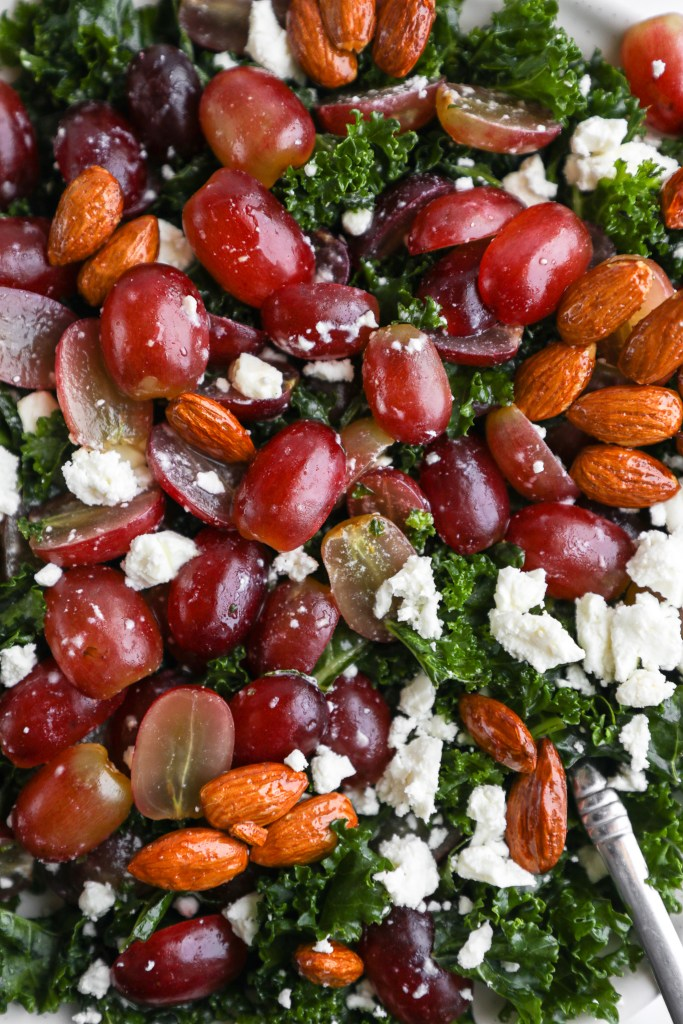 Close up of ingredients used to make a grape and feta kale salad