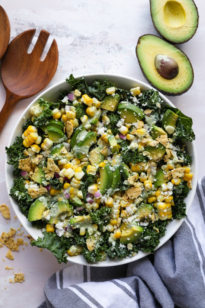 Mexican street corn kale salad served in a large bowl surrounded by sliced avocado, crushed tortilla chips and wooden serving utensils