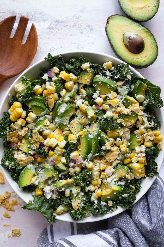 Fresh corn and kale salad sered in a large white bowl with slices of avocado and crushed tortilla chips on top