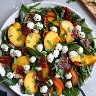 Peach, mozzarella and crispy prosciutto salad on a white plate surrounded fresh peach slices and fresh basil